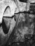Black and white bridge reflection in calm water stock images