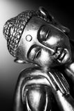 Black and white Buddha statue. A black and white image of a Buddha statue resting, in front of a dark background Royalty Free Stock Photos