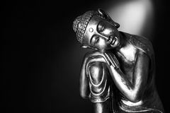 Black and white Buddha statue. A black and white image of a Buddha statue resting, in front of a dark background with a spotlight Royalty Free Stock Photos