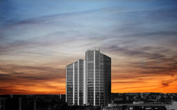 Black and white building at sunset. High-rise building on the background of the sunset Stock Images