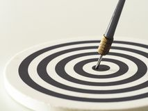 Black and white bullseye dart arrow hitting target center of dartboard. Concept of success, target, goal, achievement. Selective focus Stock Photo