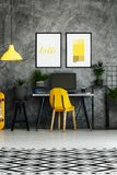 Work zone with yellow chair. Black and white carpet in contemporary work zone with yellow chair and posters on concrete wall Stock Photos