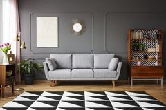 Black and white carpet with geometric pattern placed on the floor in dark living room interior with grey couch, vintage cupboard. With books and wainscoting on stock images