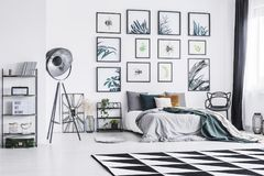 Black and white carpet placed on the floor in bright bedroom interior with king-size bed, black studio lamp and posters hanging on. The wall stock photography