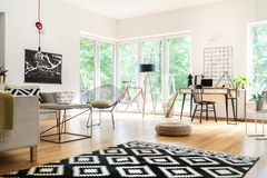Multifunctional living room with workspace. Black and white carpet and pouf in multifunctional living room with workspace, lamps and poster Royalty Free Stock Photo