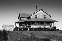 Black and white of cedar shingle house. Scary old looking cedar wood shingle farm house on top of a hill Stock Images