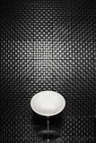 A black and white chair against a black wall. Stands on a glass floor royalty free stock image
