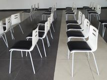 Black and white chairs rows in conference and presentation hall. On black and white floor Stock Image