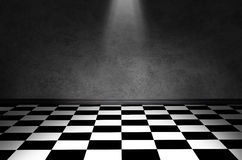 Black and white check floor. A black and white checkered floor with a textured wall and a small spotlight lighting up the center stock images