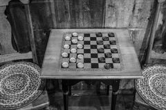 Black And White Checkers Game. Game Of Checkers. Traditional vintage style wooden checkerboard table with stools in a rural country store stock images