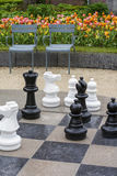 Black and white chess figures are on the chessboard with two armchairs Stock Images