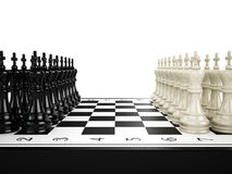 Black and white chess kings stand in a row opposite to each other on a chessboard Royalty Free Stock Image