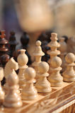 Black and white chess pieces on a chessboard, closeup. Set of chess figures on the playing board Royalty Free Stock Photos