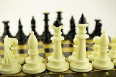 Black and white chess pieces stand on a chessboard before the start of a game. Black and white chess pieces stand on a chessboard before the start of the game stock photo