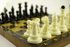 Black and white chess pieces stand on a chessboard before the start of the game. Black and white chess pieces stand on the chessboard before the start of the stock images
