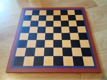 Black and white chessboard or checkerboard on wood floor. A black and white chessboard or checkerboard on wood floor stock photos