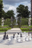 Black and white chessmen on the street chessboard with some green plants. And monuments as background Stock Images