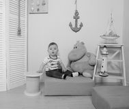 Black and white, child next to the Behemoth in the vest in the nursery. The child presents himself as a sailor in the nursery, black and White Royalty Free Stock Images