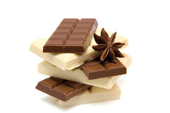Black and white chocolate. Slices of black and white chocolate with anise on white background Royalty Free Stock Photo
