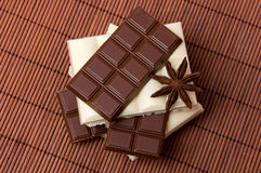 Black and white chocolate. Slices of black and white chocolate with anise on dark background Stock Photography
