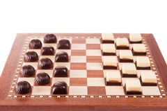 Black and white chocolates on chessboard Royalty Free Stock Photography