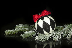 Black White Christmas Ornament. A Christmas ornament with black and white diamond pattern and red bow resting on snow covered evergreen bough on black reflective Stock Photo