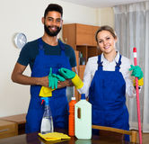 Black and white cleaners at the work. Portrait of smiling black and white professional cleaners in overalls working indoors stock photo