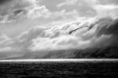 Black and white cliff beside backlit ocean Stock Image