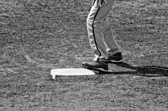 Black and white of close up of baseball base and players pants a Stock Image