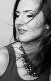 Black and white close-up of beautiful female face with colorful make-up and lips wearing jewelry and windy hair Royalty Free Stock Photo