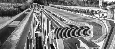 Black & white close up of bolt with cap nut, fastening the top part of a steel gate to a bridge abutment. Royalty Free Stock Photo