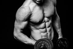 Black and white close-up of handsome power athletic mans hand stomach abs in training pumping up muscles with dumbbells Royalty Free Stock Images