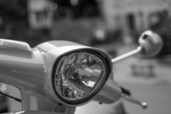 Black and white close up of the headlamp of a classic scooter with defocused background stock images