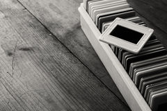 Black and white close up image of old slides frames and old camera over wooden table Stock Photos