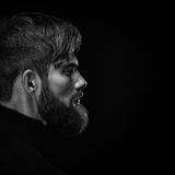 Black and white close up image of serious brutal bearded man on Stock Photos