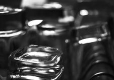 Black and white close-up image of whiskey Old Fashioned or Rocks glasses along with shot or shooter glasses on a dish drainer in t. He kitchen Royalty Free Stock Images