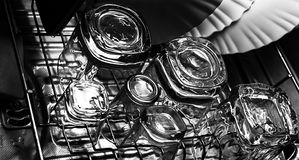 Black and white close-up image of whiskey Old Fashioned or Rocks glasses along with shot or shooter glasses on a dish drainer in t. He kitchen Stock Image