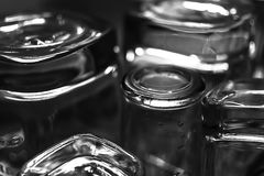 Black and white close-up image of whiskey Old Fashioned or Rocks glasses along with shot or shooter glasses on a dish drainer in t. He kitchen Royalty Free Stock Photography
