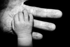 In His Hand. A black and white close up of a soft newborn baby's hand contrasted by his or her Father's gruff weathered hand stock photos