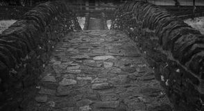 Black and white close up view of historic stone bridge from Roman times in a secluded mountain valley royalty free stock image