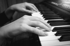 Black and white closeup of female hands on digital piano keyboard. Black and white closeup photo of female hands on digital piano keyboard royalty free stock photo