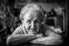 Black-and-white closeup portrait of an elderly positiv woman. royalty free stock photos