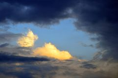 Black and White Clouds, and Blue Sky. A dramatic cloud formation, with sunset light on white clouds in patch of blue sky amongst black clouds. Hole in the sky Stock Photos