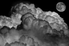 Black and white of clouds and moon. Black and white image of moon and cumulus clouds in the night Stock Photo