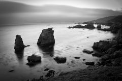 Black and white coastal shot. Incoming fog on highway 1 at sunset Stock Image