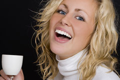Black & White Coffee. Studio shot on a black background beautiful young blond woman wearing white, laughing and drinking coffee Stock Image