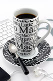 Black and white coffee mug. Black and white stylish coffee mug with coffee, mobile, headphones, keyboard, teaspoon and mat royalty free stock photos