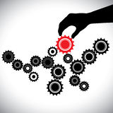 Black & white cogwheels controlled by red gear by hand(person) Stock Photos