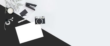 Black and white color background with flower branches, a cup of milk, earphone, pen, stapler, camera, name card and white paper. royalty free stock photo
