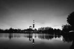 Black and white concept of beautiful floating mosque on the lake surrounded by tree and coconut tree during sunset. Stock Photo
